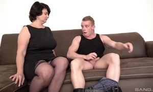 Short-haired materfamilias in stocking and high heels gives junkie exposed to burnish apply sofa